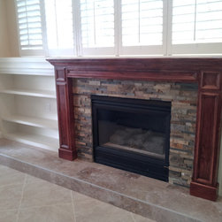 Built-in with mantel - The stone fireplace with the new, stained mantel and white bookshelves built-in.