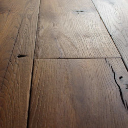 Reclaimed French Oak Wide Planks - A beautiful antique French oak floor – carefully milled from salvaged French oak beams from the Provence region in France.  Selected beams from structures dating back several hundred years are used to craft the most exclusive floors in the home building industries.  This cloister series wood floor has been scraped, brushed and lightly smoked for a deep and warm patina.  The antique French oak is perfectly suited for this finish, as cracks, nail holes and other imperfections play perfectly with the warm tone and create a floor for any French country design or Mediterranean ambiance.  Planks ranging in width up to 12″ and lengths up to 20′ will compliment open room layouts, creating the sensation of even larger rooms by avoiding seams and joints in your antique wood floor.