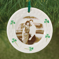 "Exposures - Custom Belleek Plate Ornament - Overview ""Pottery collectors and people who love to celebrate their Irish heritage will adore this one-of-a-kind custom Belleek plate ornament, an authentic miniature version of a Belleek plate. Crafted entirely by hand in the beautiful Fermanagh Lakelands of Ireland, Belleek pottery is prized by porcelain lovers for its egg shell delicacy and instantly recognizable translucent ivory tint of Parian china. Your photo is transferred directly onto the Irish ornament plate, transforming it into a personal keepsake. Tiny painted shamrocks, each brush stroke applied by hand, ring the photo on the personalized photo ornament. Perfect for vintage photos or travel photos from Ireland. Makes a great gift! Measures 3 1/2"" diameter. Features Belleek Pottery Shamrock detailing Parian china Each personalized ornament comes with green rope hanging ribbon Comes in a Belleek box with a story card  "" Personalization  One photo   Specifications  Measures 3 1/2"" diameter   Shipping  Please allow an additional 2 to 3 days for personalized items"