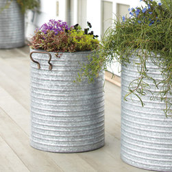 Galvanized Steel Planter - Farmhouse meets industrial meets urban chic in this galvanized planter. Made from durable steel, it can be used indoors or out. Try placing a pair filled with your favorite greenery on either side of the front door, or create a plantscape on the patio or deck. They also make excellent recycling bins, trash receptacles, or laundry hampers, as the iron handles make carrying easy.
