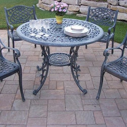 Oakland Living - 5-Pc Outdoor Round Dining Set - Includes table and four dining chairs. Metal hardware. Umbrella opening. Fade, chip and crack resistant. Warranty: One year limited. Made from rust free cast aluminum. Verdi gray hardened powder coat finish. Minimal assembly required. Chair: 21.5 in. W x 23 in. D x 34 in. H (27 lbs.). Table: 42 in. Dia. x 29 in. H (44 lbs.). Overall weight: 160 lbs.This dining set is the prefect piece for any outdoor dinner setting. Just the right size for any backyard or patio. We recommend that the products be covered to protect them when not in use. To preserve the beauty and finish of the metal products, we recommend applying an epoxy clear coat once a year. However, because of the nature of iron it will eventually rust when exposed to the elements. The Oakland Mississippi Collection combines southern style and modern designs giving you a rich addition to any outdoor setting. The traditional lattice pattern and scroll work is crisp and stylish. Each piece is hand cast and finished for the highest quality possible.