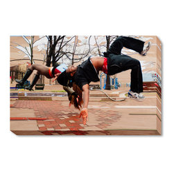 """overstockArt.com - Jazz-minh Moore - Flip Art - Enjoy this energetic ode to the beauty of the human body in motion. Reproduced from a high-quality scan of the original work, this print maintains the power and velocity of the mixed media work. The artist depicts herself and a parkour expert simultaneously back flipping in a park. This photograph was created in the second episode of second season of Work of Art: The Next Great Artist. The artist was tasked with elevating a piece of kitsch art into """"high art."""" The artist's use of painting in conjunction with the photograph helps accentuate the speed and movement of the subject. She pinpoints exactly where the eye should look and points the viewer towards the most interesting aspects of the picture. Named after Jazz music and Ho Chi Minh, Jazz-Minh spent her formative years on a hippie commune. She received her BFA from Cornish College of the Arts and her MFA from California State University, Long Beach. She has received numerous grants and scholarships, including the Elizabeth Green shields Foundation Grant. Her work has been shown at the Pulse NYC, as well as Miami, Paris, La, Seattle, Portland, and San Francisco. Her work is represented by Lyons Wier Gallery NYC, where she will be showing a solo exhibition titled """"Is That All There Is"""" in January 2012."""