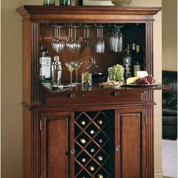 Howard Miller - Howard Miller Seneca Falls Wine Storage Bar - 690006 - Shop for Bars and Bar Sets from Hayneedle.com! What We Like About the Seneca Falls Wine Bar: This large cabinet style wine bar offers plenty of storage and serving space to accommodate any size celebration. The large drop-front of the cabinet has a lovely raised panel design on the exterior but is sturdy enough to serve as a prep area and serving area. The built-in wine rack is simply stunning as it sits flanked by two raised panel doors. The two doors conceal additional storage for the less use spirits. The fluted columns on each side of the cabinet and the antiquated hardware give this cabinet a refined traditional appeal that will fit beautifully into your home. You will be able to entertain the day away with the Seneca Falls Wine Bar.The Howard Miller StoryIncomparable workmanship unsurpassed quality and a quest for perfection - these were the cornerstones of the company Howard C. Miller founded back in 1926 at the age of 21. Even then Howard Miller understood the need to create products that would be steeped in quality and value.In 1989 Howard Miller began creating collectors' cabinets with the same attention to detail and craftsmanship inherent in their clock-making. Fashioned from glass and hardwoods Howard Miller cabinets are ideal for displaying heirlooms plates glassware and other collectibles.A highly respected brand Howard Miller maintains its popularity because of the company's commitment to quality. Every product manufactured at the company's sprawling facility in Zeeland Michigan undergoes stringent tests and exceeds industry standards to ensure a lifetime of enjoyment.