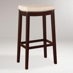 World Market - Mia Barstool - A clean linen look and an antique bronze rub trim are defining motifs of our backless Mia Barstool. Crafted of hardwood, this effortlessly graceful stool is perfect in the kitchen or as extra seating in any space.