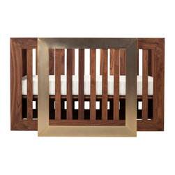 Nurseryworks - Nurseryworks Lydian Crib in Walnut Finish with 24k Gold - A 24 karat gold square base elevates the floating frame of the Halo crib. The satin sheen of the gold boldly contrasts the richness of the American sourced solid black walnut. Each piece is bench-made in a small batch production using hand-selected wood in Los Angeles. Inset end panels are constructed from walnut plywood to preserve the interior structure of the crib. One step removal of the front panel converts crib to toddler bed. Made in the US.