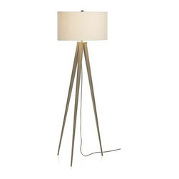 Theo Grey Floor Lamp - Tall, trim, tapered tripod takes a stand in warm grey, topped by an ample linen drum shade that adds a classic note to the modern sculpture feel. Drop-down cord in grey cloth.