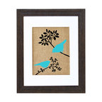 Fiber and Water - Spring Birds Art - Two graphic blue birds pop brightly against a neutral background of brown branches and natural burlap. Like the flash of a wing or the call of a songbird, this contemporary yet earthy print brings an uplifting splash of nature to your surroundings. It comes ready to hang in a distressed black wood frame and contrasting white matte.