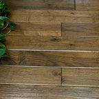 """Walnut Hardwood Flooring - Walnut flooring is an American standard well known for its dark brown heartwood, often featuring a purplish cast and darker streaks. So distinctive is the color of the Walnut hardwood that the word """"Walnut"""" itself has come to refer to this deep, rich, and highly sought after chocolate brown. One of the harder domestic species, a Walnut floor also sports a warming tone that, when combined with its rich brown tones, creates an air of tradition and classic elegance that lends itself to both modern and rustic decor. Softer than most exotic species, Walnut offers more character and deeper color than just about any other specie available."""