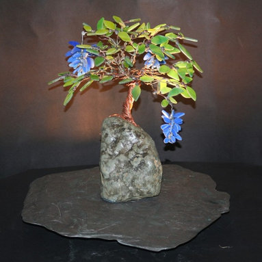Blue Wisteria Stained Glass Bonsai Tree - A Stained Glass Bonsai tree covered with green glass leaves and blue flowers.  The tree sits on top of a natural rock on its copper trunk and limbs.  The entire piece is mounted on a piece of natural slate/stone.  There is a light that lights from beneath the tree adding light to the colorful leaves and the room.