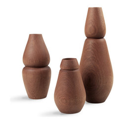 Munio Vase - Small - The Munio design series is a unique combination of beautiful, classic and timeless design with a strong environmental profile. The deep, warm and natural colors of the vases are the perfect complement to any flowers. The Vase comes in three sizes: small, medium and large. The wood used is Arura Vermelho which has a brown-reddish appearance with an occational streak of dark brown colors. The shape is sculptural and organic allowing the vase to be used as a traditional vase for flowers, or as a decorative item to be enjoyed in your home. Each vase has a porcelain insert for water that is removable for cleaning purposes.