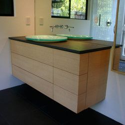 Woodland Ct. - Menlo Park, Calif. residence. Guest bath vanity in clear-finished Khaya Mahogany with stainless steel accents. Cantilevered master bath vanity in rift-sawn White Oak with clear finish over whitewash and push-release drawer hardware.