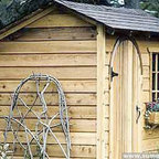 Bar Harbor Salt Box Shed - This shed is very Little House on the Prairie. I love the details like the curved doorway and the sloped roof. The planks are rough and rustic and the sizes vary so you can use it for a variety of purposes.