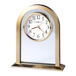 "Howard Miller - Arched Mantel Clock in Polished Brass & Glass - For the ideal statement of class, there's no better clock than this artistic, graceful piece. It features an elegantly curved arc, under which a small clock face seems to float in the midst of a clear glass center panel. The base is sturdy and good-looking, with a beveled, polished look. * This sleek table clock features a brushed and polished brass tone finished metal arch with a glass center panel and a ""floating"" dial.. The base is beveled with a polished brass finish and a brushed top surface. . The dial is white with black Arabic numerals, and brass hour, minute and second hands. A polished brass tone bezel and glass crystal completes the elegant look. . Quartz movement includes battery. . H. 7-1/2"" (19 cm). W. 6-1/4"" (16 cm). D. 2"" (5 cm)"