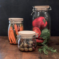 "To Have and To Hold Glass Jar - Olives, salad fixings, pickled goods—they all deserve a beautiful place to be kept. These glass jars with wood tops will do just the trick: they put the ""fun"" in functional."