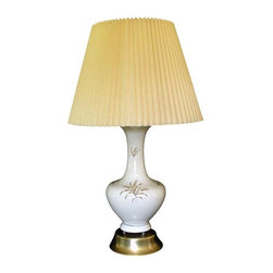 Pre-owned Mid-Century Modern White Ceramic Table Lamp - This Mid-Century Modern ceramic table lamp has a wheat pattern on the front, and the color is a warm bone hue. The lamp sits on 4 small balls attached to the base which sets it apart from other lamps of this style.  The lamp is paired with a vintage pleated shade which is in very good condition. There is an area on the base which is a lighter tone. There are very small areas of wear on the brass base. Part of the gold trim is worn on the top of the base. 19 inches to the top of the socket. the shade is 12 inches tall and 16 inches at the bottom. The lamp has the original wiring and is in very good working condition.