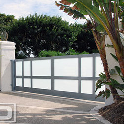 Dynamic Garage Door - Modern Style Driveway Gate With Automatic Motors Built in Steel & Frosted Glass! - Located in Newport Beach, CA, this modern style home needed a curb appeal lift. Dynamic Garage Door custom designed, crafted and installed the automatic driveway gate with white laminate glass and steel framing. The customized gate was fitted with activating devices to operate the gates at the push of a button. These driveway gates not only added curb appeal but enhanced the security accessibility to the residence.