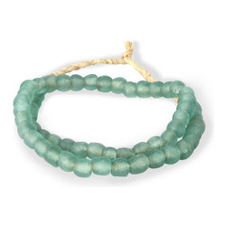 Small Teal Green Seaglass Beads - A loop of frosty sea-glass beads, their texture pitted and clouded by wind and waves, fill a knotted strand of natural fiber to make a decorative necklace that looks great draped over a vintage box of treasures, arranged around a pillar candle, or hanging on a shapely vase. This simple designer trick brings a casual, summery feel to a room without the necessity of changing out furniture or other favorite ornaments with the seasons.