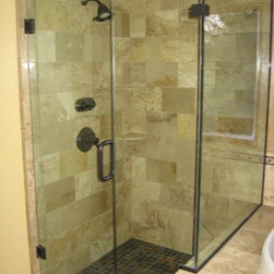 """Framless Return Shower Doors with Knee Walls - Door has wall to glass hinges with an inline notched panel that sets back over the tub deck connected to the return panel. All hardware is in oil rubbed bronze, glass is ½"""" thick."""