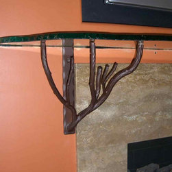 Glass Fireplace Mantel Shelf  with Chipped & Polished Edge - Unique glass shelves can be made in any shape or size to perfectly fit over your fireplace or anywhere else you're in need of a custom glass shelf.  This shelf is 74″ wide with a varying depth in irregular chipped edges ranging approx. 6-9″ deep, and the glass is 3/4″ thick.   The edging is done by hand where the glass artist literally chips away at the edge, and then hand polishes.   The shelf is supported by custom metal rests that are hand fabricated and powder coated in a deep brown finish.  Powder coating can be done in almost any color in a variety of finishes and textures.  The price for the glass shelf 74 x 9 is $940, the metal supports are $930.  Another popular size (matching up to fireplace widths) is 52 x 9, and the price for the glass in that size is $690.  Glass is custom made to order and will usually take 6 weeks to fabricate and ship.    Glass is custom packaged in-house, ships via UPS Freight with a 1 to 4 day transit and will range in price between $149 – $225 depending on destination.
