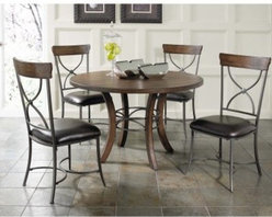 Hillsdale Cameron 5 Piece Round Wood Dining Table Set with X-Back Chairs - Dark gray metal provides a beautiful complement to the chestnut brown wood finish of the Hillsdale Cameron 5 pc. Round Wood Dining Table Set with X-Back Chairs. This gorgeous wooden table has a metal accent between its gracefully curved legs. The chairs each feature a gray metal frame and faux leather upholstery with a wooden accent on the chair back. This set seats up to four people comfortably and makes a great centerpiece for any dining room. About Hillsdale FurnitureLocated in Louisville Ky. Hillsdale Furniture is a leader in top-quality affordable bedroom furniture. Since 1994 Hillsdale has combined the talents of nationally recognized designers and globally accredited factories to bring you furniture styling and design from around the globe. Hillsdale combines the best in finishes materials and designs to bring both beauty and value with every piece. The combination of top-quality metal wood stone and leather has given Hillsdale the reputation for leading-edge styling and concepts.