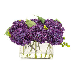 Purple Beauty Botanical - A vibrant posy of purple hydrangeas heralds the arrival of summer's long awaited beauty. Vivid green leaves peek out from amidst the full-bodied blooms. The sleek glass rectangular vessel, holding a splash of faux water, allows this faux botanical to be easily placed along a window ledge or a slender occasional table; a collection of multiples creates a stunning centerpiece for your garden party table.