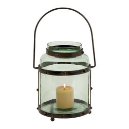 Metal Glass Lantern with Solid Metal Frame - Add this metal glass lantern to your room interiors as it exudes charm and class in the best way. It is made from high quality iron that has rusted details for a striking appearance. The metal glass lantern features a unique design structure that involves a plain transparent glass body and a metal frame. The plain glass used for a bright reflection of the flame allows more light to pass and illuminate the room. The pointed studs act as a steady stand for the lantern. The wide candle holder in the center of the structure with a wax candle gives a unique touch to this lantern. You can gift this candle to your dear one and top it up with a sweet note to keep it besides the bedside. It comes with following dimensions:
