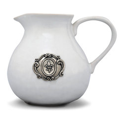 Medici Pitcher - White - A bold fleur-de-lis in a wreath of scrollwork brings European heraldry to any upscale table. The pewter medallion which graces the side of the Medici Pitcher, a curvaceous vessel in pure white ceramic, unifies this serving piece with your heirloom pewter ware or, alternately, your juleps cups while the snowy glaze contributes to a well-appointed table in any season.