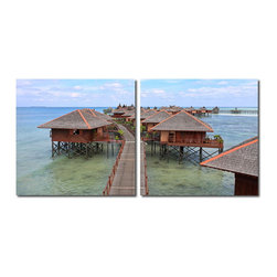 """Wholesale Interiors - Idyllic Resort Mounted Photography Print Diptych - A string of luxurious overwater bungalows stretches into the sea and toward the horizon in this whimsical photograph. Made in China with MDF wood frames, this two-piece modern wall art set features an image split in half and printed on two waterproof vinyl canvases. The Idyllic Resort Photo Diptych is made in China and is fully assembled. Hardware for hanging on the wall of your choice is not supplied. To clean, wipe with a dry cloth. Product dimension: 19.68""""W x 1""""D x 19.68""""H."""