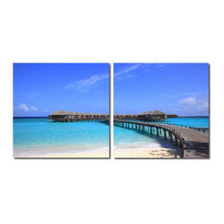 """Wholesale Interiors - Bridge to Paradise Mounted Photography Print Diptych - Lining the horizon in this photograph is a collection of lavish overwater bungalows, the epitome of relaxation in the tropics. This is a diptych: a set of two frames intended to be hung together on a wall. Each MDF wood frame is fitted with half of the image printed on a sheet of waterproof vinyl canvas. The Bridge to Paradise Modern Wall Art Set is made in China and is fully assembled. Hardware for hanging on the wall of your choice is not supplied. To clean, wipe with a dry cloth. Product dimension: 19.68""""W x 1""""D x 19.68""""H."""