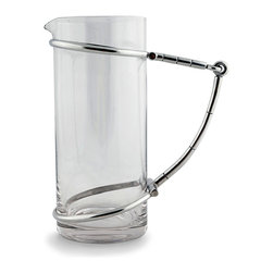 Bit Glass Pitcher - Bring equestrian detail to your table in a surprising new form with the Bit Glass Pitcher, a cylinder of glass with a neatly-limited spout confined by an oversized rendition of the classic symbol of elite stable culture. The horse bit, which is made from pewter, not only embellishes the pitcher with decisive straight lines but provides a generously-sized figural handle.