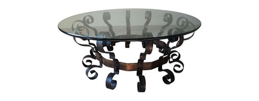 """Pre-owned Scrolled Metal & Glass Coffee Table - This substantial Mediterranean style scrolled iron and round glass coffee table from the Late 1960s makes quite the statement! Solid and heavy iron base with gilded detail and a 3/4"""" thick round glass table top. In very good vintage condition. Please note, there is some surface wear to the glass rim."""