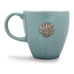 Coquille Mug - Mist - A single accent point on the wall of the Coquille Mug in Mist is the first element of this graceful, forward-thinking breakfast cup to catch the eye, but the richness and fanciful detail of this formal pewter medallion is only one part of the piece's impact. Made from fine stoneware, hand-glazed and twice-fired, this elegant mug makes after-dinner coffee a contemplative, exquisite occasion.