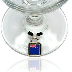 """Made on Terra - Flag of New Zealand Wine Glass Silver Charm - Your guests have arrived and the atmosphere is electric. A sip of wine here, a sip of a cocktail there and you find the conversation turning to the charming baubles you've placed on the glasses, something special you chose for each of your eclectic guests. They love them and appreciate your thoughtfulness. You love them for their uniqueness and that no one forgets which glass they were using.  Choose from Made on Terra's many designs for the best party ever. Ring is 1"""" diameter; measures 2"""" from top of ring to bottom of charm. Made of metal and plastic. Sold individually."""