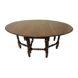 """Used Exquisite Antique Style Gate Leg Dining Table - This large solid oak dining table is handcrafted of the absolute finest quality; beautiful solid wood with a glowing hand rubbed finish and a lightly distressed effect to the top. The really lovely turned legs and stretchers are made with tenon joinery. The gate leg function operates smoothly. When the leaves are lifted the gate legs swing open easily; stop-gap blocks under the leaves ensure that the gate legs are positioned properly and secure when open.  Cutouts in the stretchers ensure a flat and secure fit when the legs are closed.    This table is heavy and large, beautiful and fine in every way.    Dimensions when open:  Width: 82""""  Depth: 62.5""""  Height: 30""""    Dimensions when folded:  Width: 62.5""""  Depth: 25""""  Height: 30"""""""