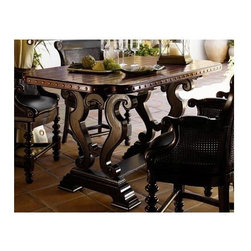 Tommy Bahama Home - Sienna Bistro Table - This table has a unique design which combines elegant details with rustic appeal. Features decorative nail head trim and a scrolled base combined with a contrasting distressed black base and distressed brown top. Spacious enough to host all your dinner guests in style. True Hand hewn top. Decorative nail head trim. Bottom of apron to floor 33.75 in.. Base highly distressed black finish. Top lightly distressed wood finish. Made from mahogany solids, American maple and mahogany veneers. Casis finish. Minimal assembly required. 64 in. L x 38 in. W x 36 in. H (167 lbs.). Special Care Instructions from Lexington Furniture. Assembly InstructionsA balance of point and counterpoint defines the Sienna Bistro table, with the hand-hewn plank top balanced by more formal scrolling in the base and the warm burnished Cassis finish above that glows against the dark Tamarind finish below. Kingstown is a relaxed traditional collection inspired by British Colonial style, with a hint of Campaign and a touch of safari. The Tamarind finish is a rich aged black with rub-through to crimson and gold undertones beneath. The evocative designs provide a sense of a well-traveled life.of items hand selected during journeys around the globe.