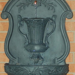 Ladybug - Urn Wall Fountain in Gray Finish - Includes pump and tubing. Weather resistant finish. Wall-mounted. 1-Year warranty. Made in USA. Made of pecan shell resin. 18 in. W x 8 in. D x 29 in. H (19 lbs.)The finishes are applied by hand, enhancing every detail, and resulting in the uniqueness of no two pieces being exactly alike. Each individually hand-crafted piece of Ladybug product is cast in a crushed marble or resin composition which has the ability to capture and reproduce the same definition and minute detail as the original. It is a substantial, non-porous material which does not absorb moisture, making it ideal for outdoor use, although it offers the strength and durability required to endure even extreme weather conditions.