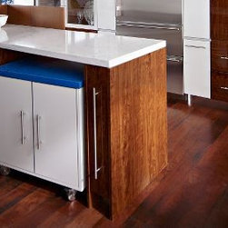 Pantone's Colors of the Year - Heritage Hickory – Brandywine: The rich wood stain of the cabinetry and matching kitchen flooring creates a dramatic backdrop for the modern focal points of the room: a white slab countertop, steel drawer pulls and dazzling blue painted walls.