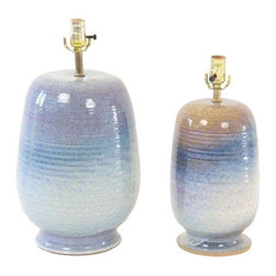 """Pre-owned Mid Century 1960s Beachy Blue Pottery Lamps - Pair - When you switch on this pair of lovely lamps, you can practically hear the crashing waves of the ocean! These rich, glazed pottery lamps are two different sizes, the larger lamp featuring blue tones and the smaller lamp featuring blues and beige. It's hard not to let the imagination drift away to a seaside sunset. Both lamps are newly rewired, dating back to the 1960s. Condition is good with normal wear due to age. Made of ceramic in the USA.    Large lamp: 6"""" dia. x 19"""" H  Small lamp: 6"""" dia. x 16"""" H"""