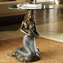 Mermaid Accent Table - Equal parts fantasy and functionality, our bewitching Mermaid Accent Table consists of a wide, circular glass surface atop the beautifully detailed, verdigris-toned mermaid holding a spiral seashell. Stunning overall appearance makes this enchanting aquatic treasure the perfect unique accent to take your decorating to a whole new level.