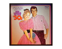 """Glittered 75s Music Album - Glittered record album. Album is framed in a black 12x12"""" square frame with front and back cover and clips holding the record in place on the back. Album covers are original vintage covers."""