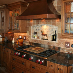 Kitchens - Knotty alder kitchen cabinets with copper range hood and tile backsplash by Anliker Custom Wood, Ltd.