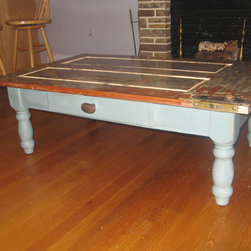 Custom Rustic Furniture - Custom ordered coffee table from an antique farm door from the early 1800's.  Table top has been skillfully resurfaced to display evolution of colors and styles that the door has bared over the last 200 years.  Table includes heavy farm table legs, a storage drawer and antique brass door knob as a drawer pull.