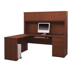 "Bestar - Bestar Prestige + 5-Piece L-Shape Desk in Cognac Cherry - Bestar - office Sets - 9987276 - The Prestige + Collection features a steadfast value and a traditional design. Ideal for every type of office including home office the credenza and return are designed with durable 1"" commercial grade work surfaces with a melamine finish that resists scratches stains and burns as well as a shock resistant 0.1""PVC edge. Adding to these details are an efficient wire management system with grommets classic ribbed side moldings and a large work surface. The matching hutch offers plenty of closed storage space large enough to fit letter-format binders. The hutch doors are fitted with strong adjustable hinges. The fully-reversible pedestal has two utility drawers and a file drawer that's able to store letter- and legal-sized paper. All drawers are fitted with double extension ball-bearing slides for smooth openings. The built-in lock secures the two bottom drawers. This desk also includes a keyboard shelf with double-extension ball-bearing slides and a CPU platform. This unit meets or exceeds AINSI/BIFMA performance standards. Also available in Chocolate or Bordeaux and Graphite finishes."