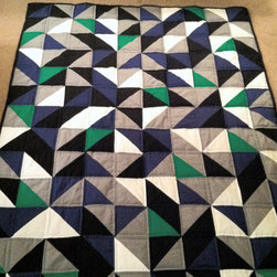 Modern Geometric Quilt by Ewe Have Me in Stitches - Lest you believe quilts can only be feminine, I present this awesome example that is modern, geometric and masculine. It would look so great in so many settings — imagine it folded on the back of a cognac leather couch.