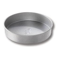 USA Pans 9 Inch Round Cake Pan - The USA Pan 9 inch cake pan has been designed with many of the same standard features of industrial baking pans. Each pan is constructed of aluminized steel the material of choice for commercial bakeries. Metal thicknesses have been selected that allow even heat distribution and maximum service life. Our pans also use steel wires in the rim construction of most pans to provide additional strength and resist warping. Each pan is coated with AMERICOAT© Plus a proprietary silicone coating that nearly all North American bakers prefer over dark non-stick coatings. AMERICOAT© Plus is a clear non-stick environmentally friendly coating that is specifically formulated for superior baking and does not contain any PTFE's or PFOA's. USA Pan bakeware features a corrugated or fluted design. The corrugation maximizes pan strength and prevents warping denting and other effects of everyday use. Corrugation also minimizes surface contact with baked goods which translates into an evenly baked product that is easily released. USA Pan has been developed by the world's largest manufacturer of industrial bakeware and has been providing the world's leading commercial bakeries with the highest quality baking pans for over 50 years. When you purchase a USA Pan you are buying products that meet industrial standards for innovation quality and durability. Put simply our pans are the best available and are proudly produced in the UNITED STATES OF AMERICA.