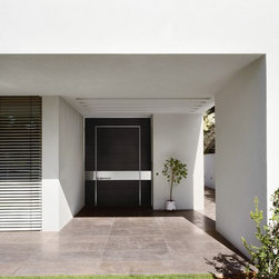 Oversized black front door from Oikos's Synua collestion - Synua is an Italian-designed safety door on a that pivots as it opens. Available in large sizes up to 86 inches wide and 118 inches high. Designed by Adriani&Rossi.