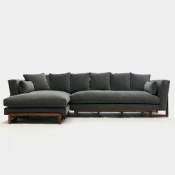 Artless - Artless | LRG Sectional Sofa - Made in Los Angeles by ARTLESS. The LRG Sectional Sofa is by far their most plush sectional from ARTLESS. This modern sectional is full of comfort and invites you to immerse yourself in the soft, down alternative cushion and pillows. The large sofa sectional is designed with all four sides in mind, so it looks great from any angle. Solid walnut base and back cradle the sofa and complete this visually striking seating solution. Each LRG Sectional Sofa is individually bench built in Los Angeles and is available in your choice of fabric.