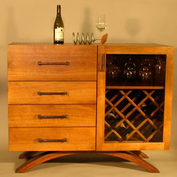 Mid Century Sideboard - Midcentury wine cabinet with bent lamination legs. 4 full extension soft close drawers, dovetailed maple. Soft close hinges on door as well with room for 15 bottles, glasses and accouterments. The cabinet sports mitered corners for a seamless grain following pattern from sides to top. Fitted with antiqued solid brass handles and finished in a Cashmere stain.