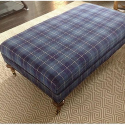 Used Ralph Lauren Plaid Upholstered Ottoman - This is a beautiful one of a kind ottoman. It has hardwood turned legs on brass casters. Its upholstered in a beautiful Indigo and Navy Blue fabric by Ralph Lauren called Palm Harbor.     It can a coffee table with books and a tray. Or it can be used to rest your tired feet and enjoy some TV time. It is very durable and chic!