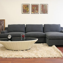 Wholesale Interiors - Kaspar Slate Modern Sectional Sofa - Contemporary sectional sofa. Slate gray twill upholstery. Wood frame. High-density polyurethane foam cushioning. Upholstery covers are fully removable. All pillows can be removed, repositioned, and their fabric covers unzipped. Black wood legs with non-marking feet. Ships on pallet 40 in. W x 48 in. L x 127 in. H. Overall: 122.25 in. W x 57.60 in. D x 28 in. H. Chaise: 57.60 in. W x 44 in. D x 28 in. H. Seat: 106.5 in. W x 46.25 in. D x 17.75 in. H . Assembly requiredKaspar's width and comfort make it the sofa you will look forward to relaxing on every evening! This contemporary sofa is large enough to seat at least five adults with room to spare. Constructed with care, the modern sectional starts with a solid wood frame, foam cushioning, and black wood feet. Trendy, goes-with-everything gray twill upholsters the sectional and is made to be removable with Velro if the need arises. In addition, all cushions can be removed as well as their twill covers. Non-marking feet finish off the set. Note: the sofa and chaise are freestanding and do not secure to one another.